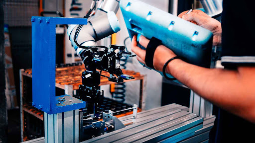 A cobot being trained through manual manipulation to assist workers