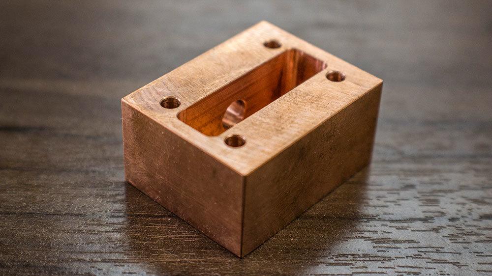 Small copper-colored CNC part